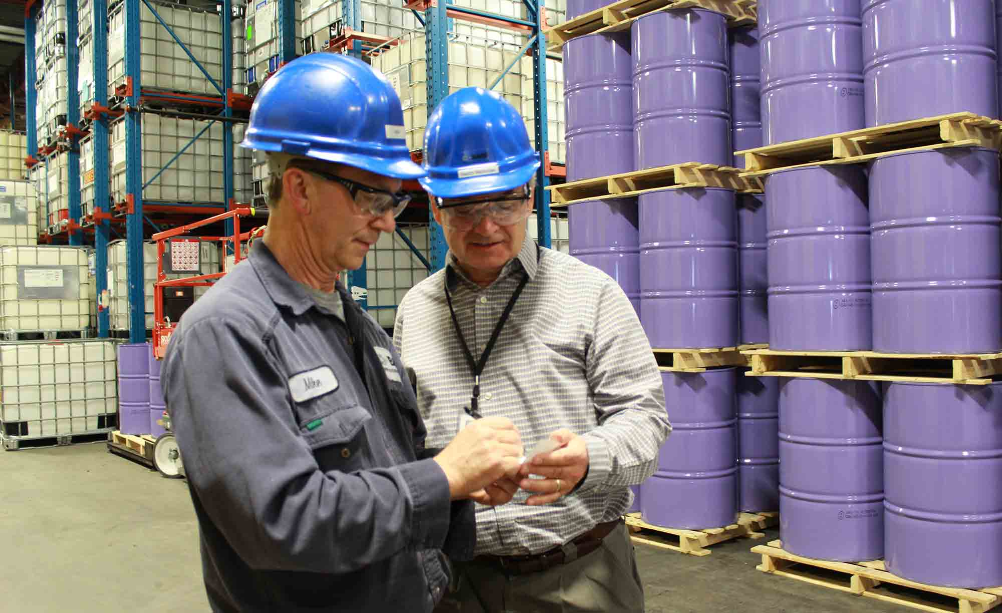 BASF employees Mike Smith, Production Supervisor, and Barry Nicholas, Toronto Site Manager, review inventory levels in the warehouse of BASF's Toronto site.